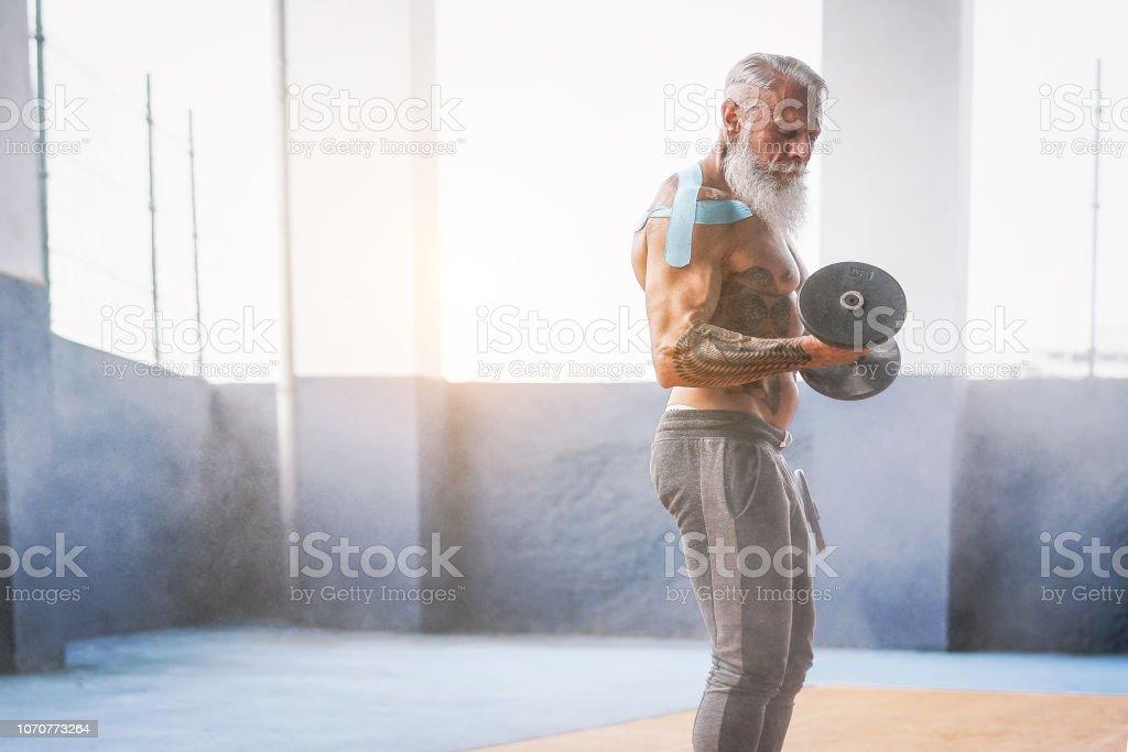 Homem de barba de aptidão fazendo bíceps curl exercício dentro de um edifício de corpo - homem tatuagem sênior de treinamento com halteres em centro de wellness club - ginástica e esporte serve conceito - foto de acervo