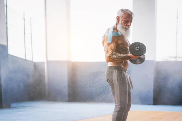 fitness bart mann bizeps curl übung in einem fitness-studio - tattoo senior woman training mit hanteln im wellness-club-center - bodybuilding und sport fit-konzept - alte tattoos stock-fotos und bilder