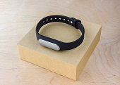 Fitness bracelet on the box of the kit. A smart bracelet pedometer and a box from it on a wooden table.