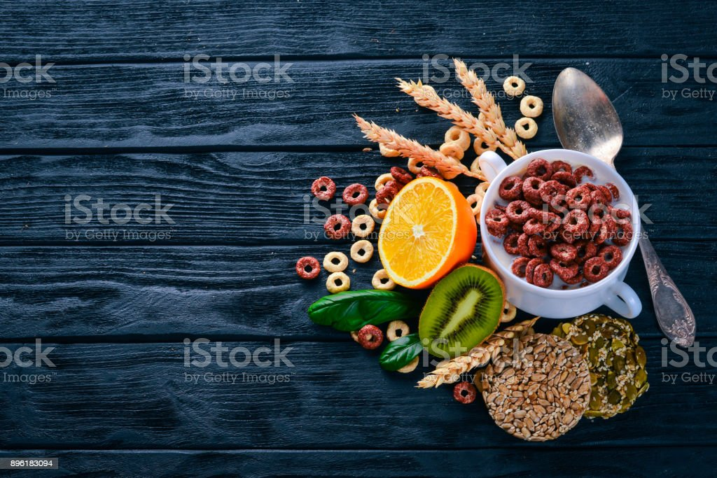 Fitness breakfast, muesli, milk, fruits, nuts and seeds, on a wooden surface. Top view. Free space for text. stock photo