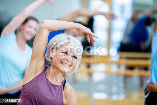 A group of adults are indoors at a fitness center. A woman in the foreground is wearing casual exercise clothing, and smiling while doing stretches.