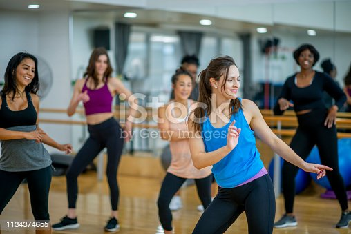 A diverse group of women dances in their fitness class. They are all laughing while their hands are stretched out to the side.
