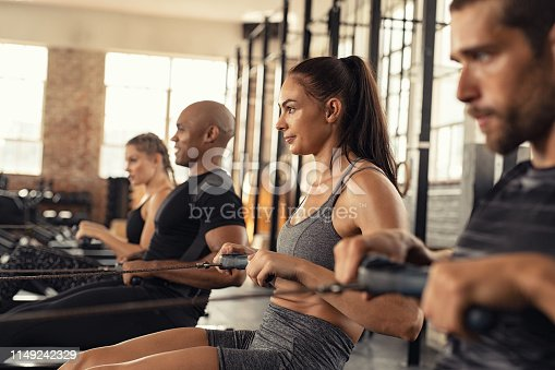 Group of people exercising in gym using rowing machine together. Side view of sportswoman doing exercise on rowing machine in cross training center. Muscular girl and sporty men workout on training simulator at gym gym.