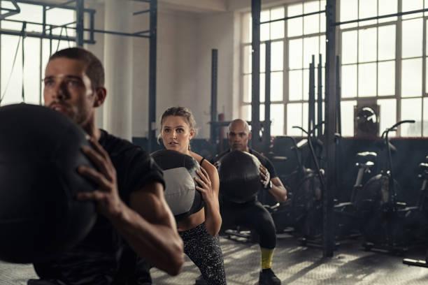 fitness class using heavy weight balls - class стоковые фото и изображения