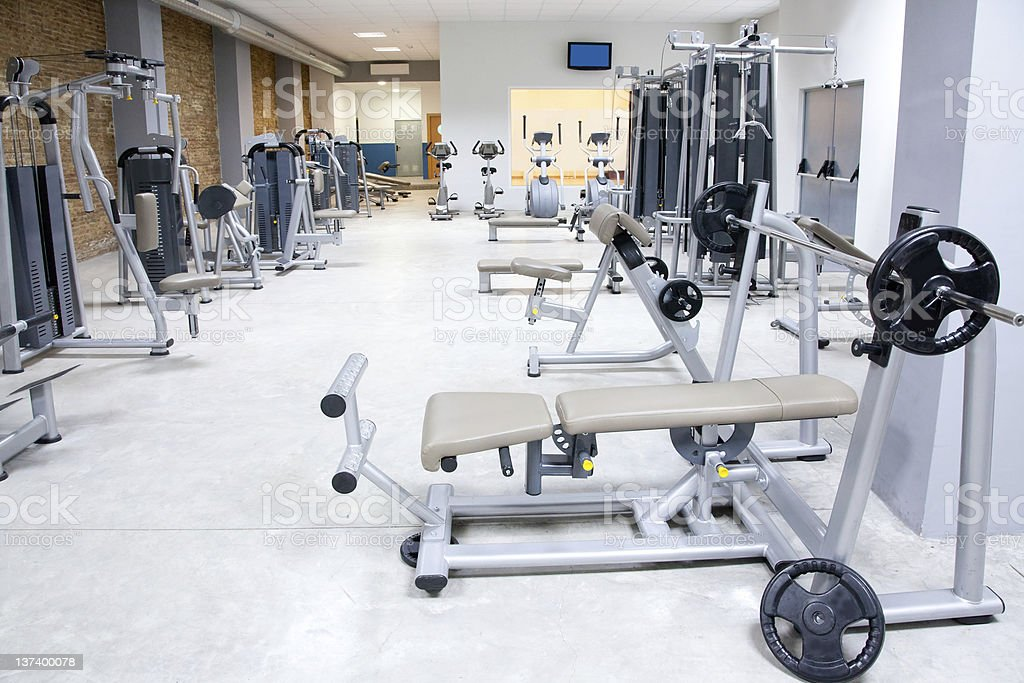 Fitness club gym with sport equipment interior stock photo