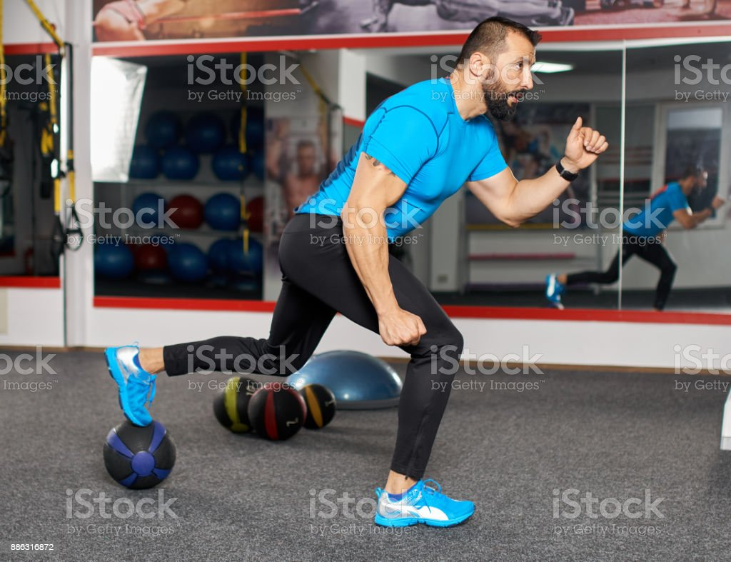 Fitness coach executing lunges with heavy ball stock photo