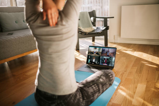 Fitness coach teaching yoga online to group of people Fitness coach teaching yoga online to group of people. Yoga trainer demonstrating yoga poses to students via video conference. exercising stock pictures, royalty-free photos & images