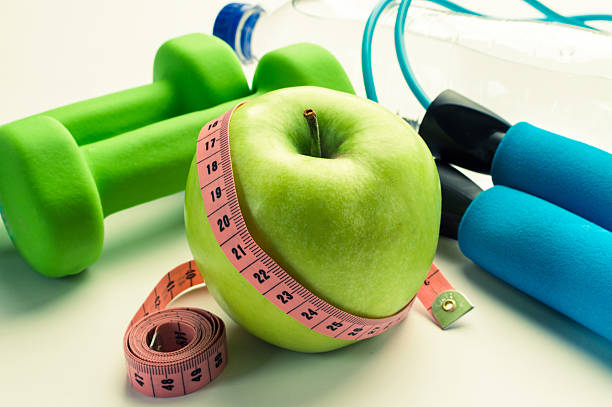 Fitness concept - apple with dumbbells, measuring tape and stethoscope