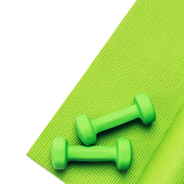Fitness concept - green yoga mat and dumbbells