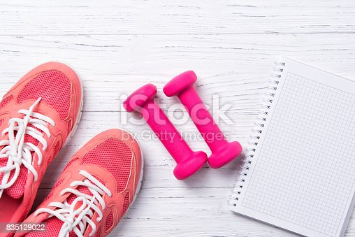istock Fitness concept, pink sneakers and dumbbells with notebook on wooden background, top view with copy space 835129022