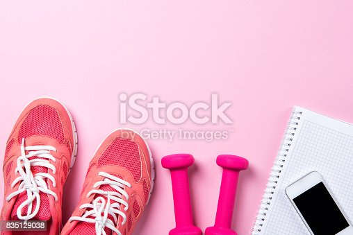 istock Fitness concept, pink sneakers and dumbbells with notebook with smart phone on pink background, top view with copy space 835129038