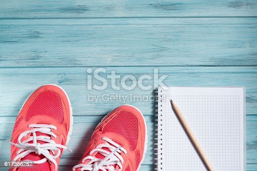istock Fitness concept, pink sneakers and notebook with pencil 617386282