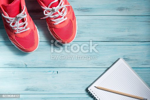 istock Fitness concept, pink sneakers and notebook with pencil 622808412