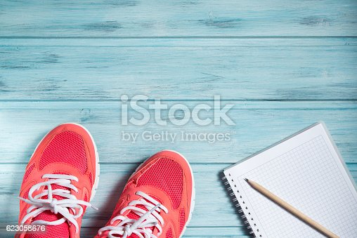 istock Fitness concept, pink sneakers and notebook with pencil 623058676