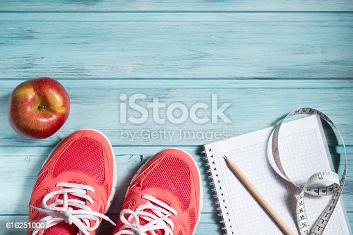 istock Fitness concept, pink sneakers, apple and notebook and measuring tape 616251000