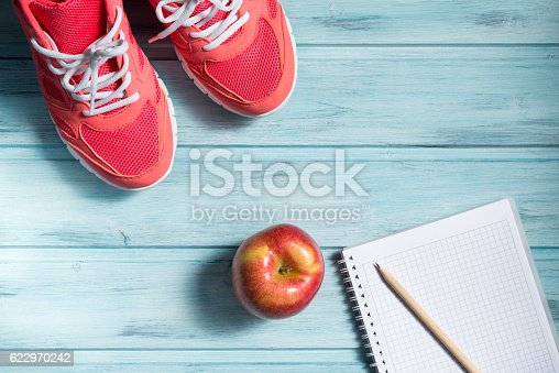 istock Fitness concept, pink sneakers, apple and notebook with pencil 622970242