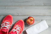 Fitness concept, pink sneakers, apple and white towel