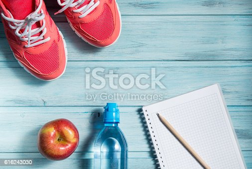 616251000 istock photo Fitness concept, pink sneakers, apple, bottle of water and notebook 616243030