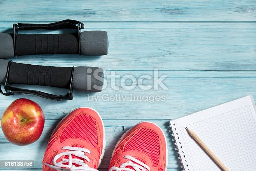 istock Fitness concept, pink sneakers, apple, dumbbells and notebook with pencil 616133758