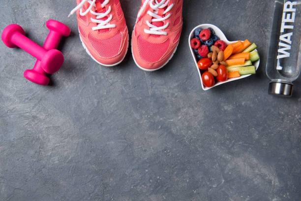 fitness concept, pink sneakers, dumbbells, bottle of water and heart shaped plate with vegetables and berries on a grey background, top view, healthy lifestyle - fitness imagens e fotografias de stock