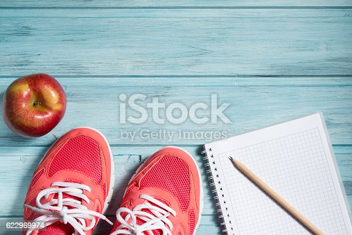 istock Fitness concept, pink sneakers, red apple and notebook with pencil 622969974
