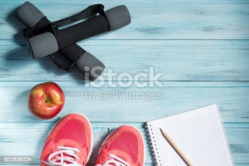 istock Fitness concept, pink sneakers, red apple, dumbbells and notebook 622808204
