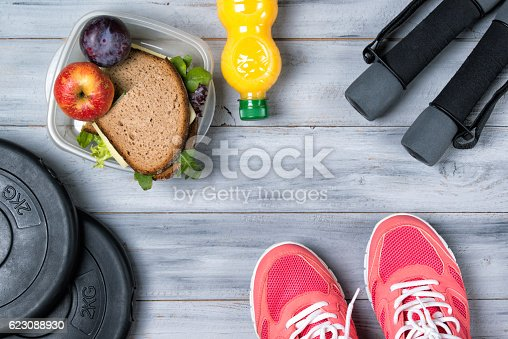 istock Fitness concept, pink sneakers, weight plates, dumbbells, sandwich 623088930