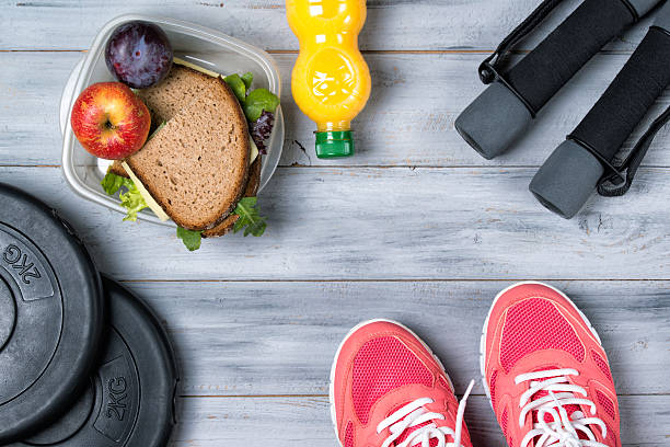 fitness concept, pink sneakers, weight plates, dumbbells, sandwich - relaxation exercise stock photos and pictures