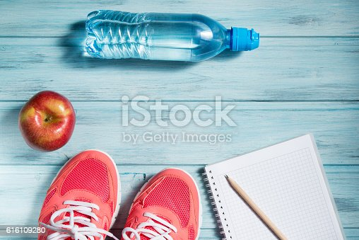 616251000 istock photo Fitness concept, sneakers, apple, bottle of water and notebook 616109280