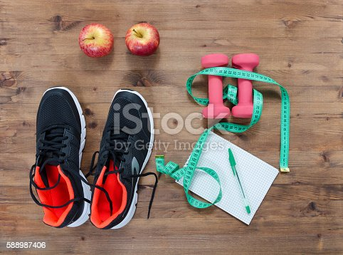 istock Fitness concept with sneakers notebook  apple and measure tape 588987406