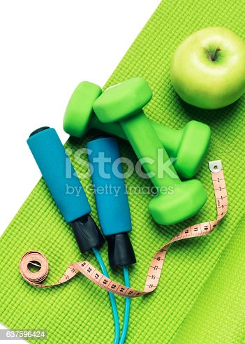 637596492 istock photo Fitness concept - yoga mat, apple, dumbbells and skipping rope 637596424