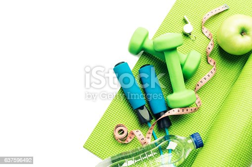 istock Fitness concept - yoga mat, apple, dumbbells and skipping rope 637596492