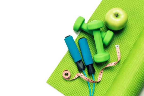 Fitness concept - yoga mat, apple, dumbbells and skipping rope