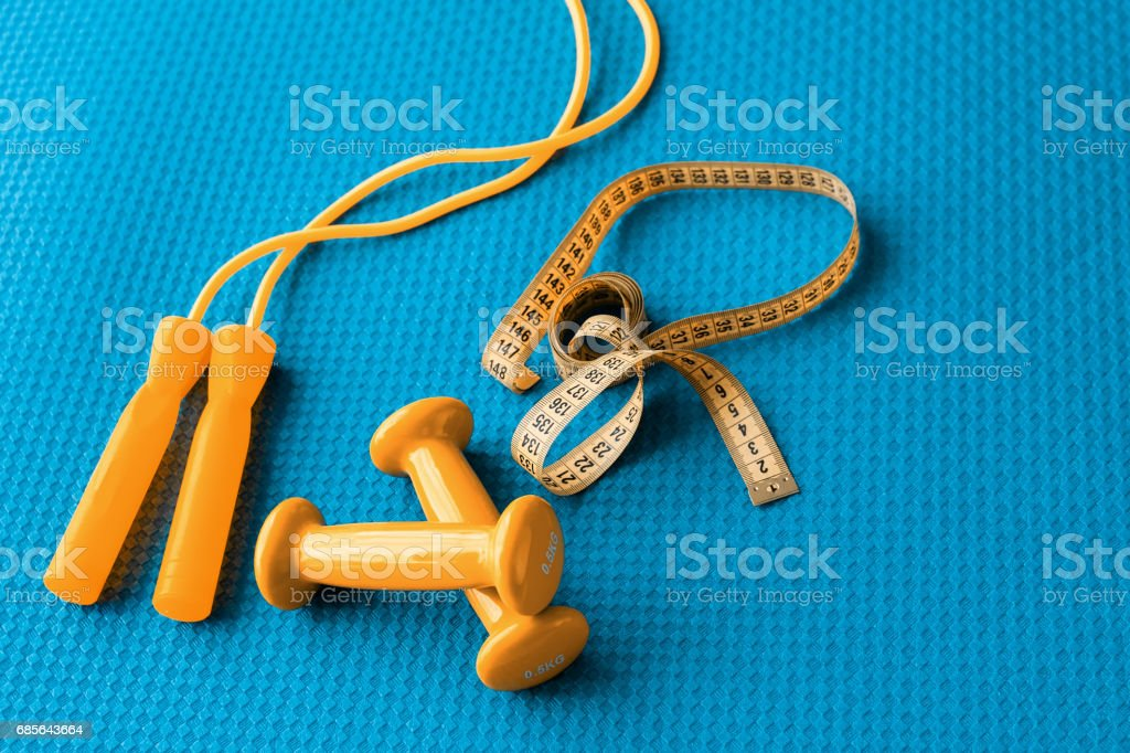 Fitness concept - yoga mat, dumbbells, skipping rope and tape measure ロイヤリティフリーストックフォト