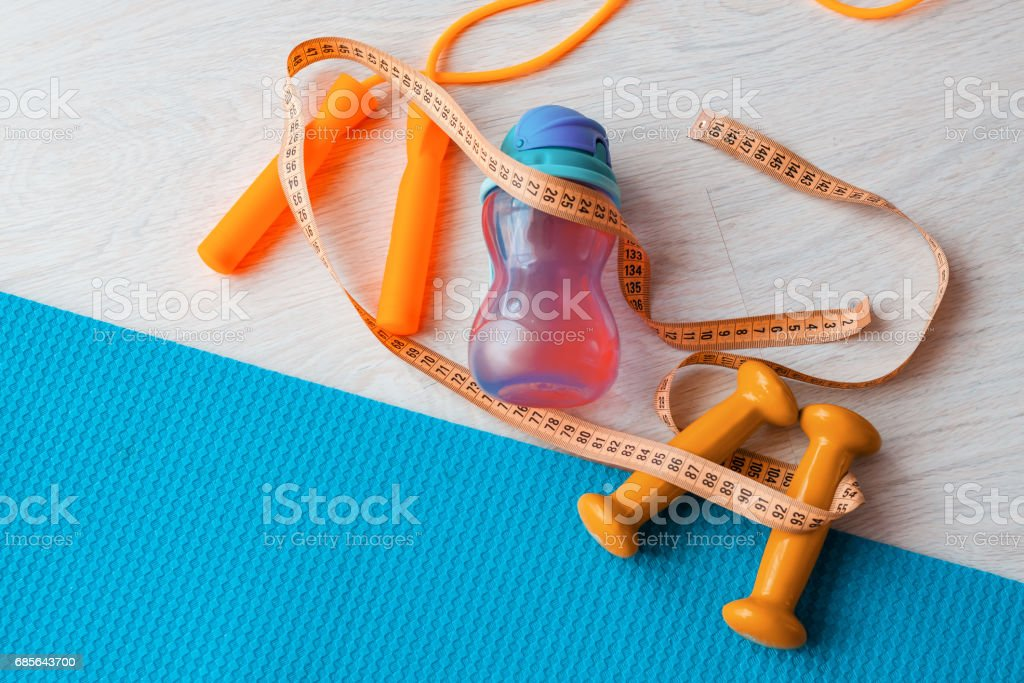 Fitness concept - yoga mat, dumbbells, skipping rope, water bottle and tape measure royalty-free stock photo