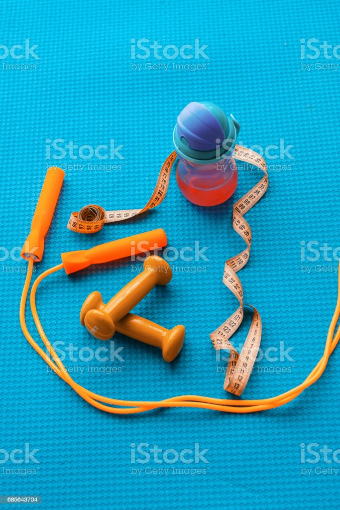 Fitness concept - yoga mat, dumbbells, skipping rope, water bottle and tape measure 免版稅 stock photo