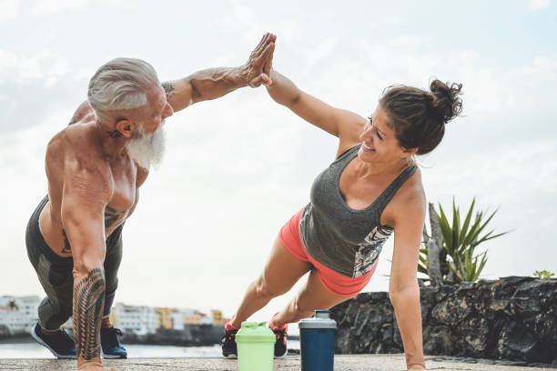 fitness couple doing push ups exercise outdoor - happy athletes making workout session outside - concept of people training and bodybuilding lifestyle - active lifestyle stock pictures, royalty-free photos & images