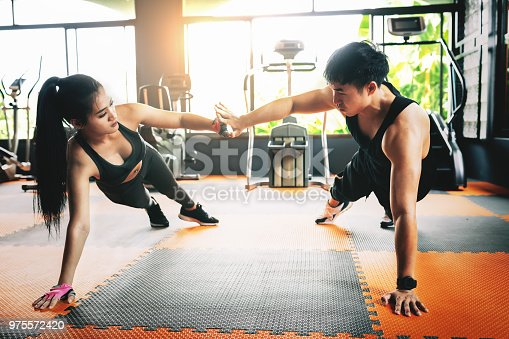 istock Fitness couple in sports dress doing fitness. 975572420