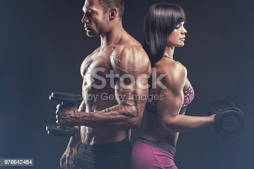 Bodybuilding couple exercise with dumbbells on a black background