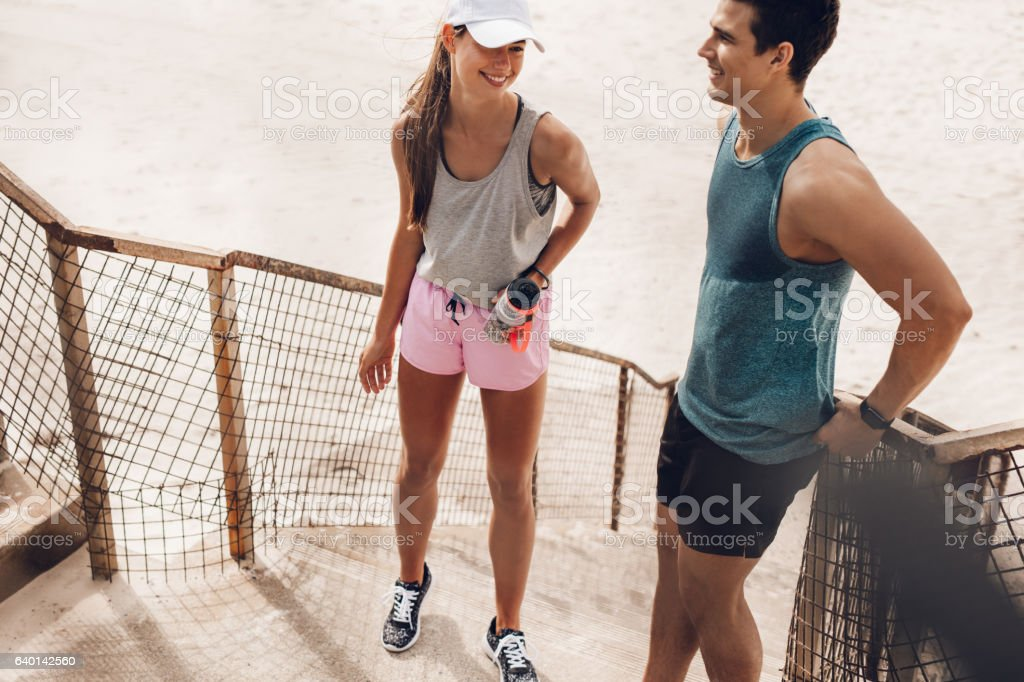 Fitness couple resting and talking at the beach stock photo