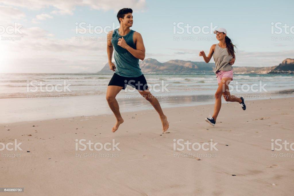 Fitness couple running on the beach stock photo