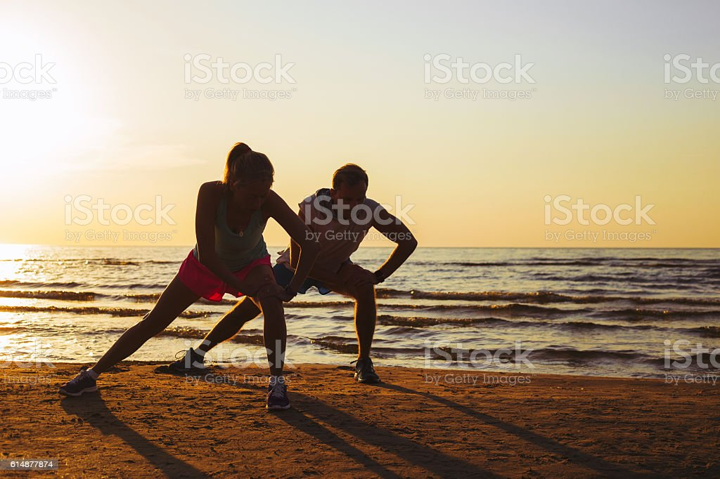 Fitness couple stretching in sunset stock photo