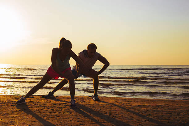 fitness couple stretching in sunset - being in a relationship with someone is going to require stock photos and pictures