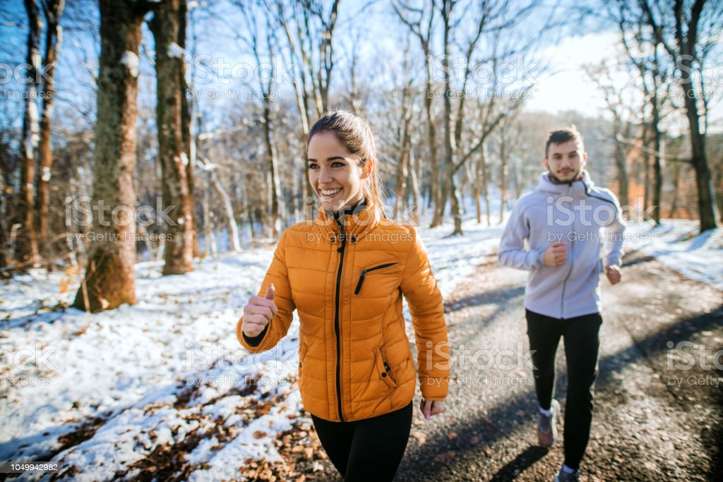 Fitness couple winter morning exercise at snowy mountain. stock photo