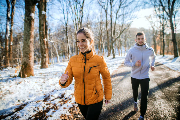 fitness-paar winter frühsport am verschneiten berg. - kalte sonne stock-fotos und bilder