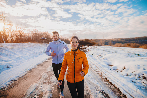 Fitness couple winter morning exercise at snowy mountain.