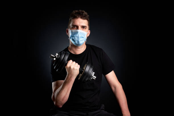 fitness despite covid-19 young man exercising with dumbbell despite corona wearing a protective mask despite stock pictures, royalty-free photos & images