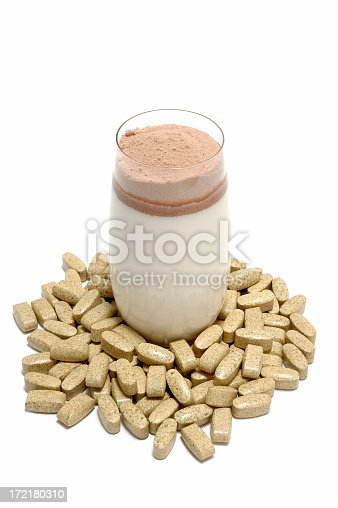 Glass of milk with portion whey protein, surrounded with tablets of fat burner.