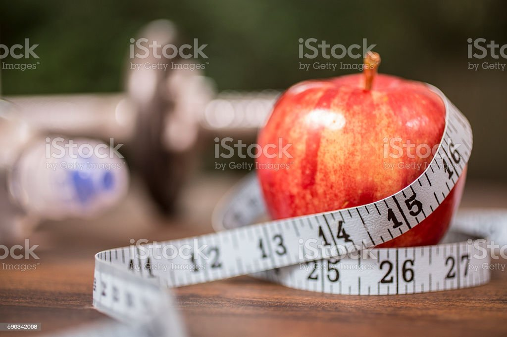 Fitness, dieting themed scene with apple and tape measure. royalty-free stock photo