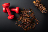 istock Fitness equipment and coffee. Fitness skipping rope and red dumbbells. 1288985264